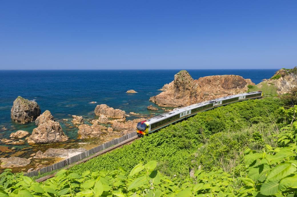 Rund um die Welt gibt es atemberaubende Bahnstrecken. Im Bild zu sehen: Ein Zug der Gonō Line in Japan, der im Norden des Landes an der Küste entlangfährt.