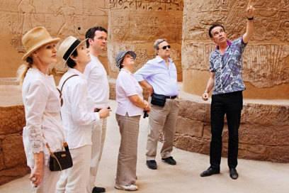 Ein Lektor führt die Gäste von Hapag-Lloyd durch einen Tempel in Ägypten – Landausflüge sind eine Möglichkeit fürSingles, andere Reisende kennenzulernen