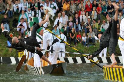 Mit langen gepolsterten Stangen stoßen sich verkleidete Fischerstecher in die Donau