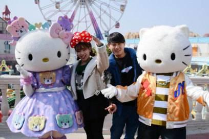Li Yuyang (r.) und Lu Ni lassen sich mit Hello-Kitty-Figuren fotografieren. In dem neuen Park inChina entkommt man der Comic-Katze nicht