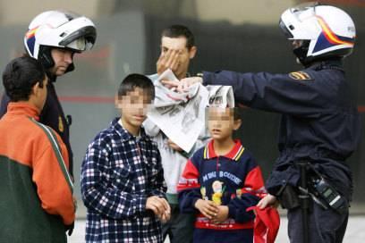 Polizisten in Madrid mit einer Gruppe Jungs, die des Taschendiebstahls bezichtigt werden