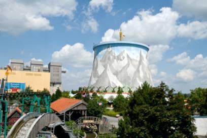 """Das Herzstück von """"Kernie's Familienpark"""" ist der 46 Meter hohe Kühlturm, der mit einem Alpenpanorama bemalt ist. Im Inneren befindet sich ein Karussell, an der Außenwand kann man klettern."""