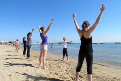 Eine Fitnesstrainerin gibt am Strand von Cesenatico einen Pilateskurs