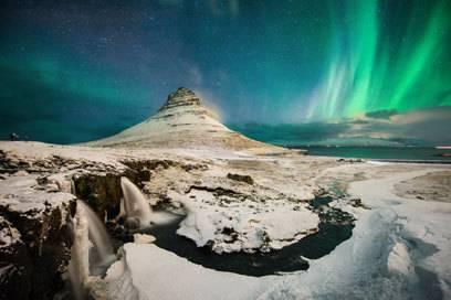 Der Berg Kirkjufell, hinter dem Polarlichter bunt leuchten