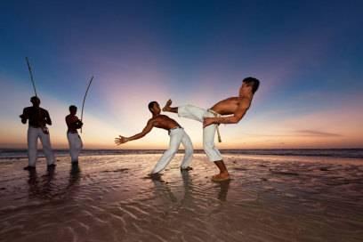 Capoeira-Kämpfer am Strand: Das Instrument, das die Männer im Hintergrund spielen, heißt Berimbau und gibt den Rhythmus und damit die Geschwindigkeit des Kampfes, Spiel genannt, vor
