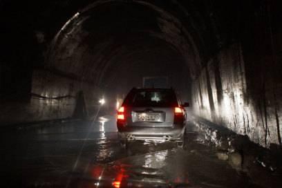 Ein Auto im Tunnel. Die Röhre ist eng, die Fahrbahn überflutet, und eine Beleuchtung fehlt gänzlich.