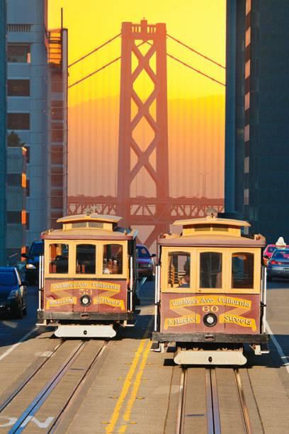 Zwei Cable Cars im Sonnenaufgang, mit der Oakland Bridge im Hintergrund