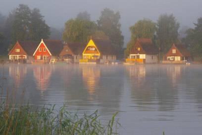 In den Morgenstunden herrscht bei Frühnebel eine mystische Atmosphäre am Mirower See. Hier gibt es Ferienhäuser direkt am Wasser – mehr Natur und Erholung geht nicht!