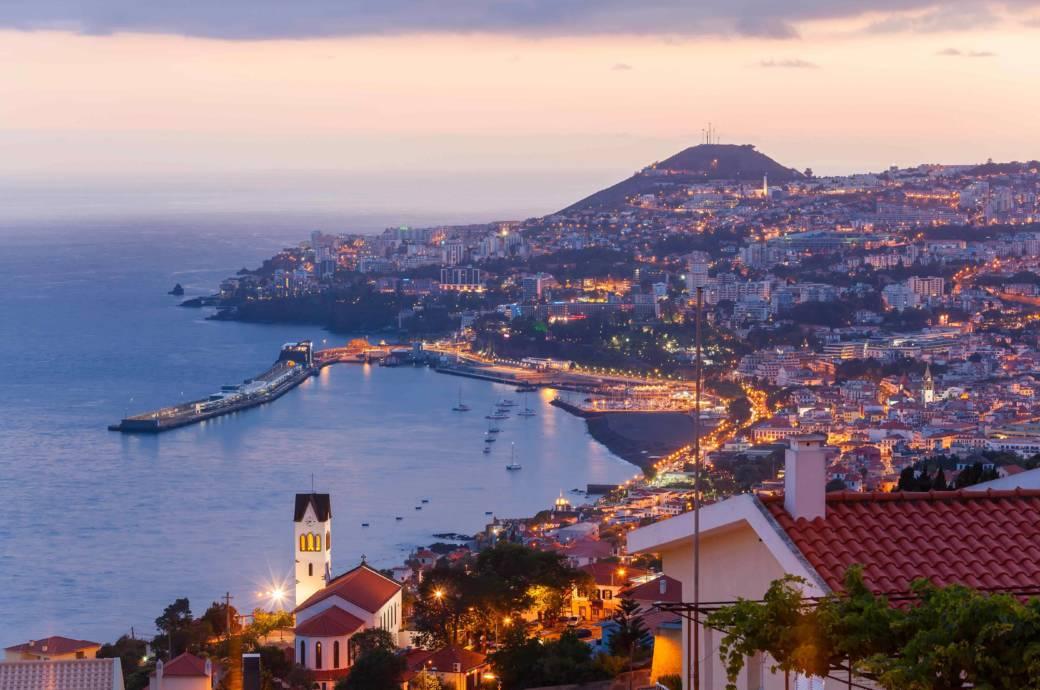 """Blick über die Bucht von Funchal im Abendlicht. Ihren Namen (dt. """"viel Fenchel"""") erhielt die Insel-Hauptstadt, weil hier bei der Entdeckung durch die Portugiesen besonders viel dieser Gemüse- und Gewürzpflanze wuchs"""
