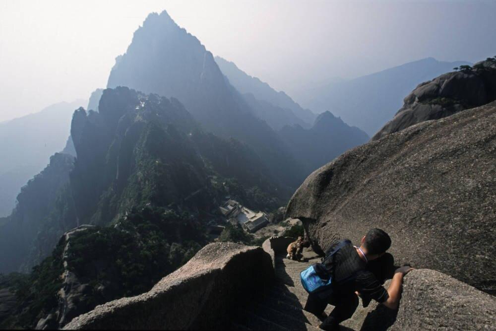"""Nervenkitzel, wohin man geht und schaut: Der abschüssige Weg im Huangshan-Gebirge führt über steinerne Stufen zum 1864 Meter hohen Lotusblütengipfel, dem höchsten von insgesamt 72 Gipfeln in den """"Gelben Bergen"""" (links)"""