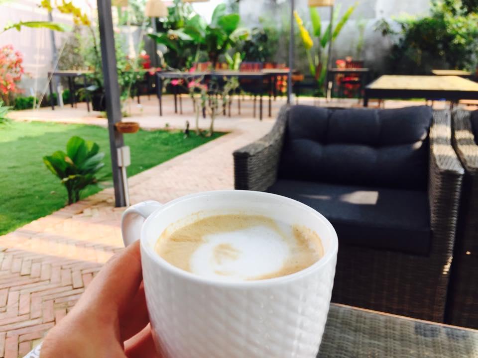 Digital Nomads: Kaffeetasse mit Cappuccino, im Hintergrund Gartenmöbel