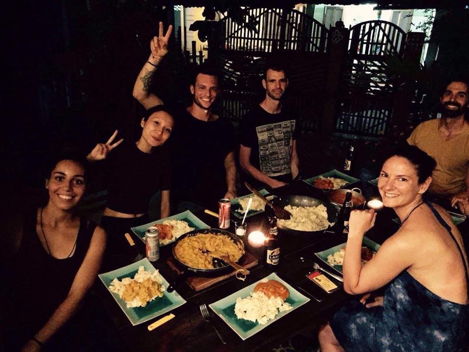 Auswandererpaar: mit Gästen am Tisch sitzen, gemeinsam Kochen und Essen