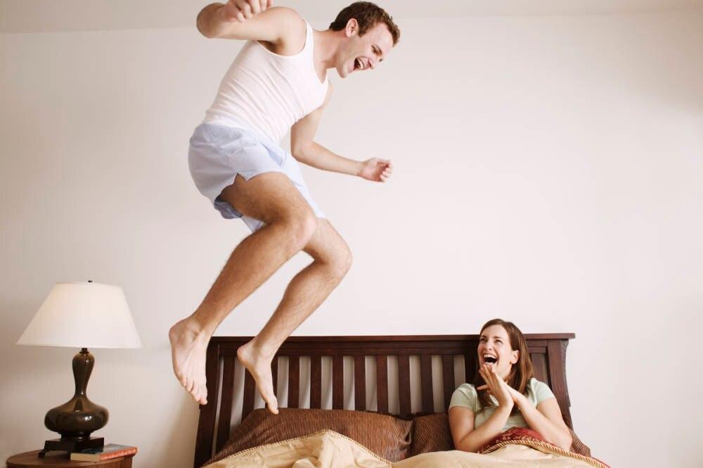 Mann springt auf dem Bett im Hotel