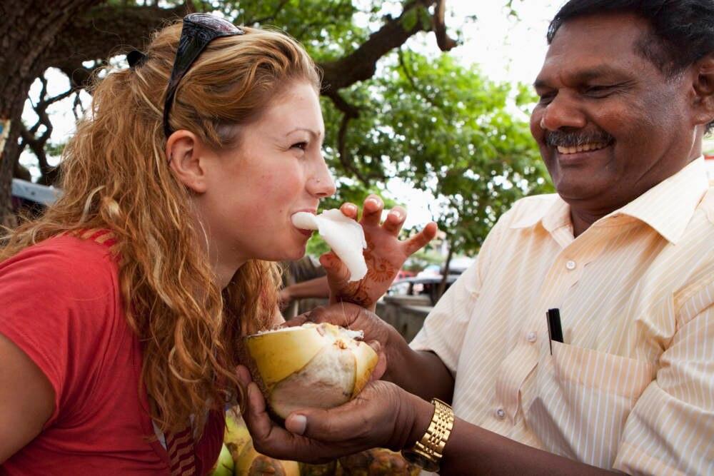 Alleine reisen: Frau beißt in Frucht vor indischem Mann