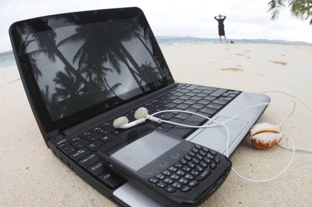 Laptop und Handy am Strand