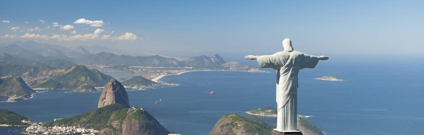 Der Corcovado mit der Christusstatue und der Zuckerhut (im Hintergrund) sind die Wahrzeichen von Rio de Janeiro