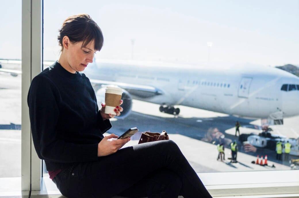 Eine Frau sitzt mit einem Kaffee am Flughafen und schaut auf ihr Handy