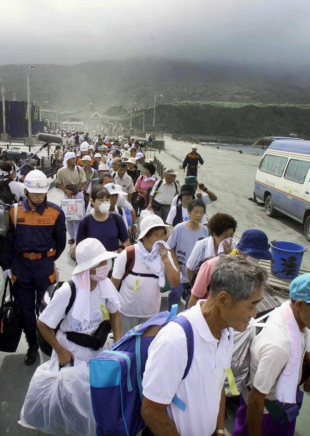 2. September 2000: Die Evakuierung hat begonnen. Die Inselbewohner warten, teils mit Atemmasken, auf die Fähre, die sie zum Festland bringt