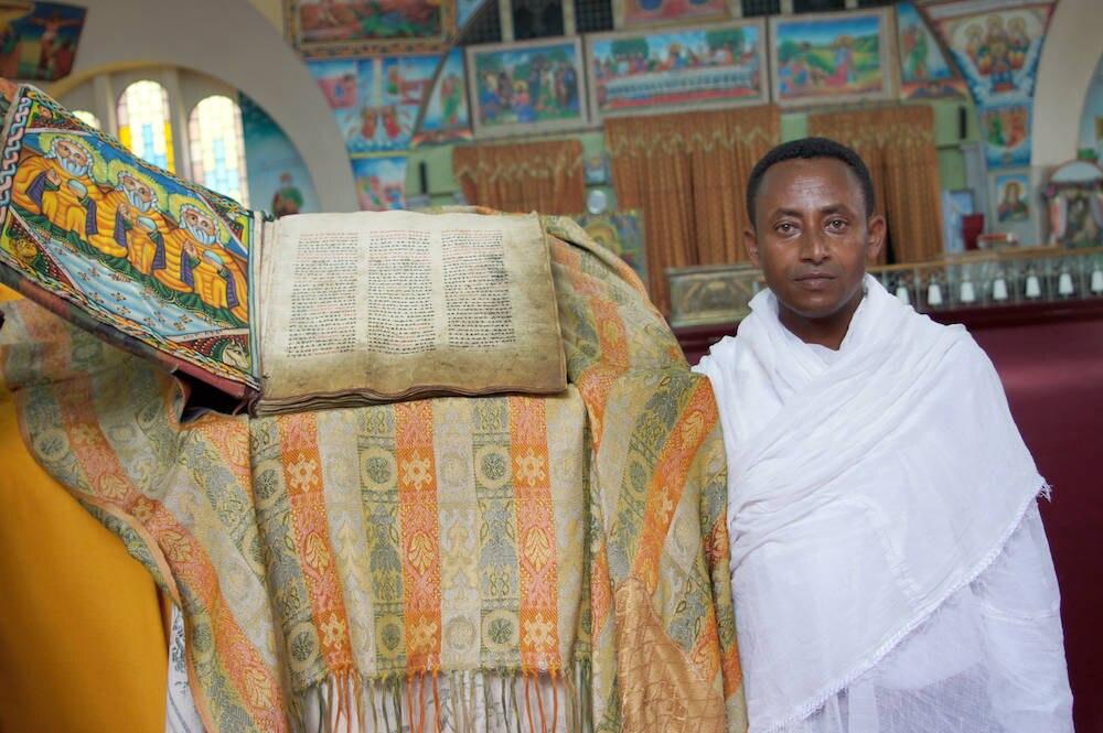Diakon Zemikael Brhane in der neuen Kirche der Heiligen Maria von Zion in Axum neben einem alten religiösen Buch