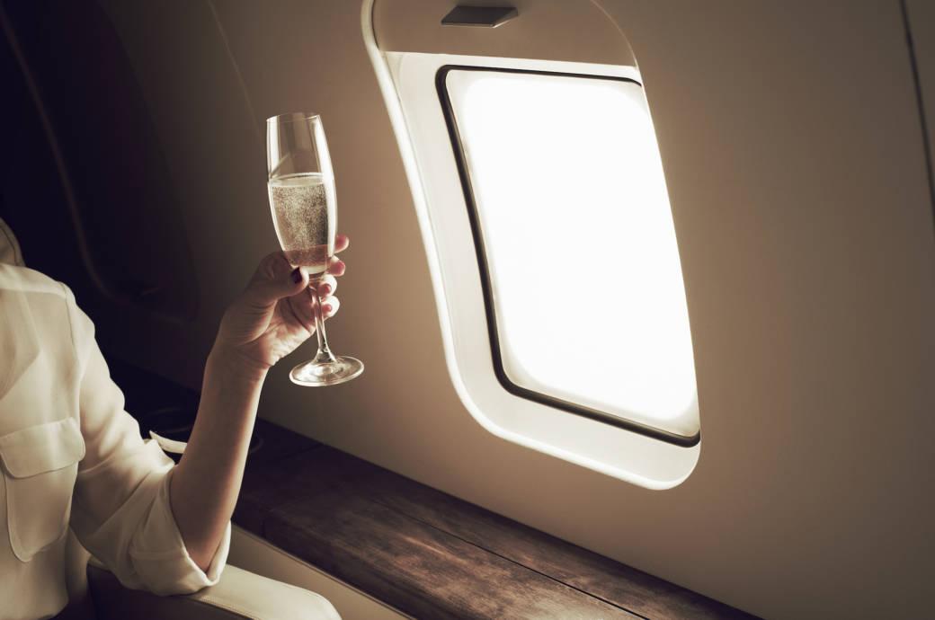 Frau trinkt Champagner im Flugzeug