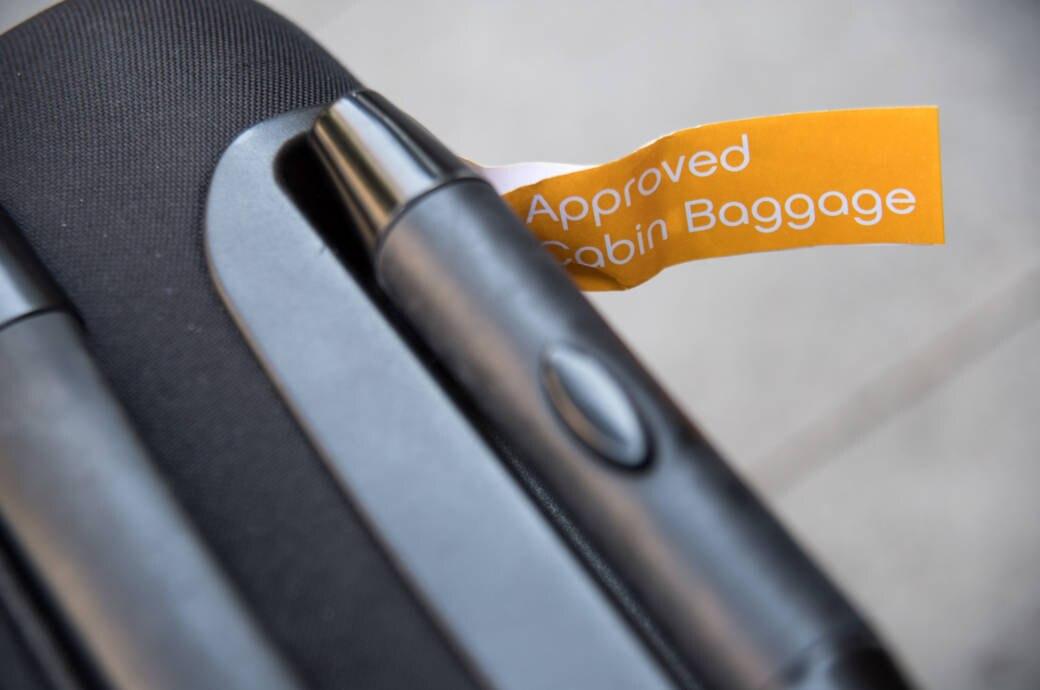 Warum bekommt das Handgepäck vor dem Check-in ein Bändchen?
