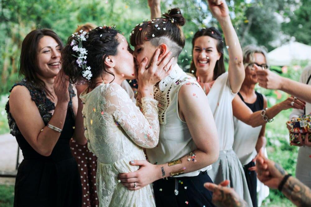 Ein gleichgeschlechtliches Paar küsst sich auf einer Hochzeit
