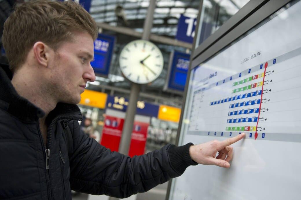 Mann schaut am Bahnhof auf den Wagenstandsanzeiger
