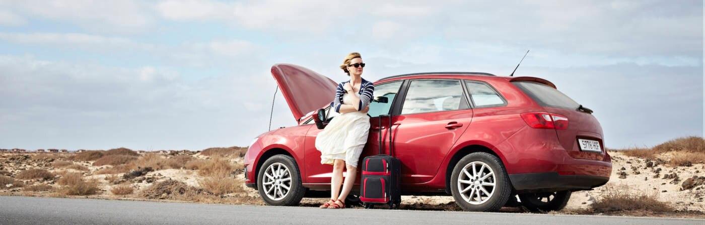 Frau steht am Straßenrandneben kaputtem Auto