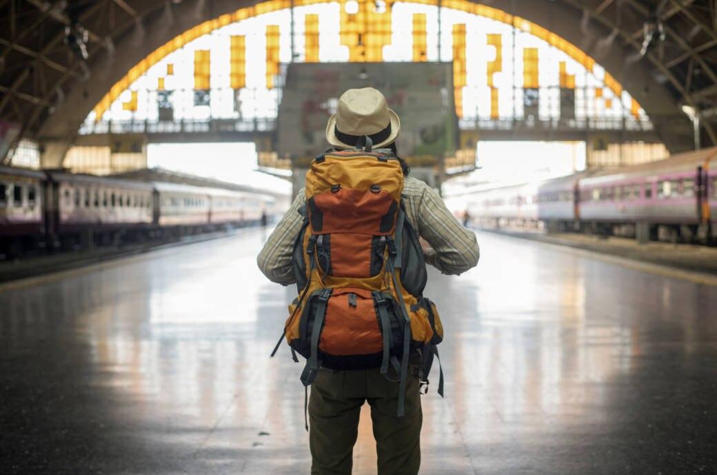 Backpacker mit Rucksack am Bahnhof