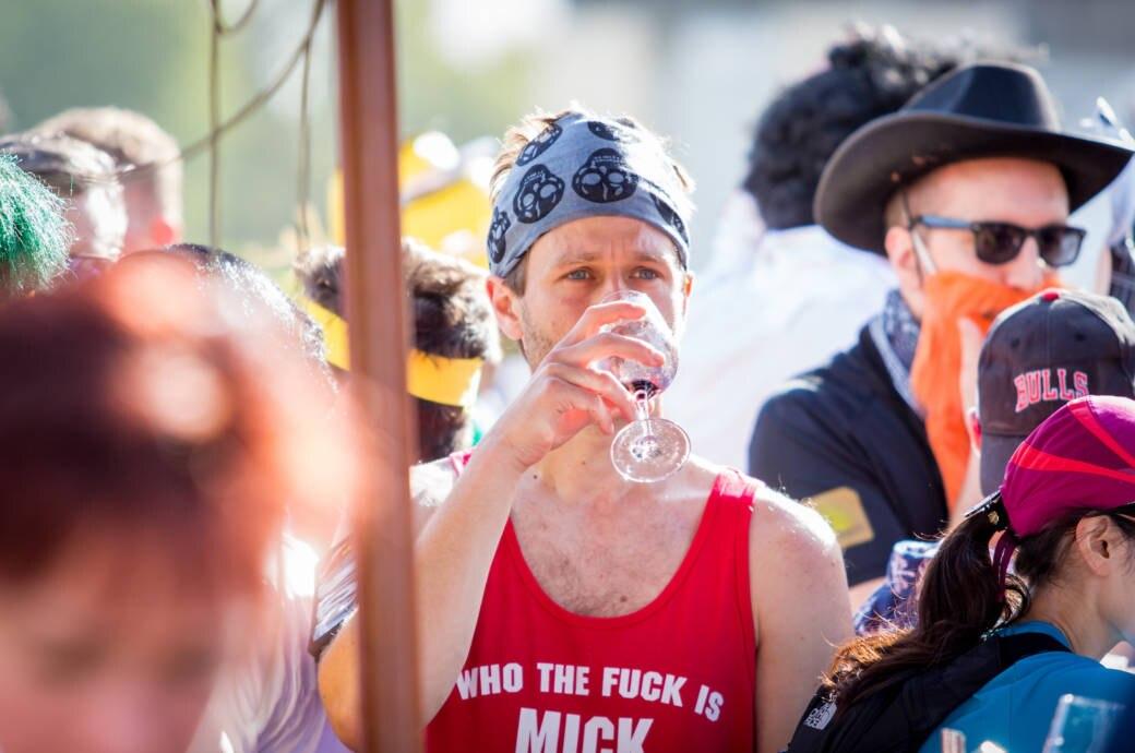 Läufer trinkt Wein beim Marathon du Médoc