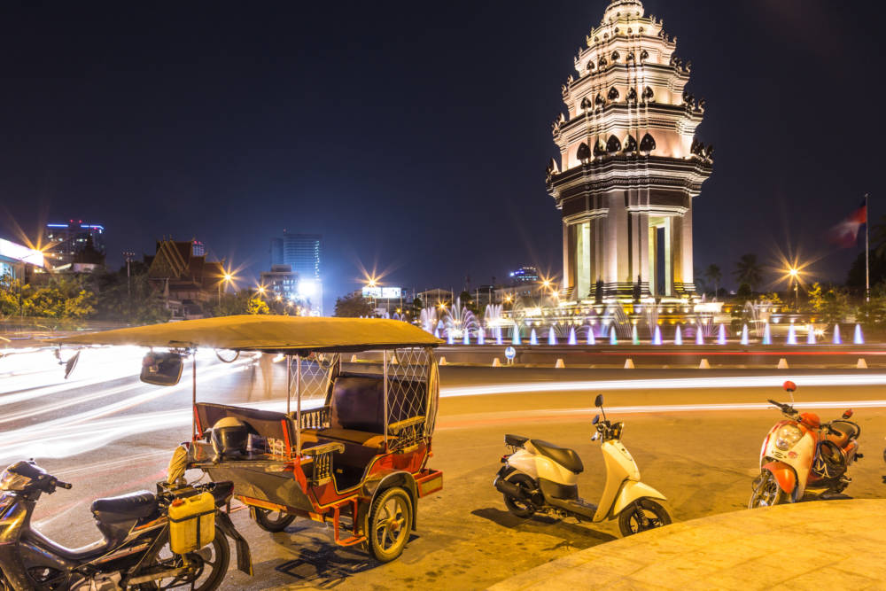 Ein Tuk Tuk vor dem Unabhängigkeitsdenkmal in Kambodschas Hauptstadt Phnom Penh