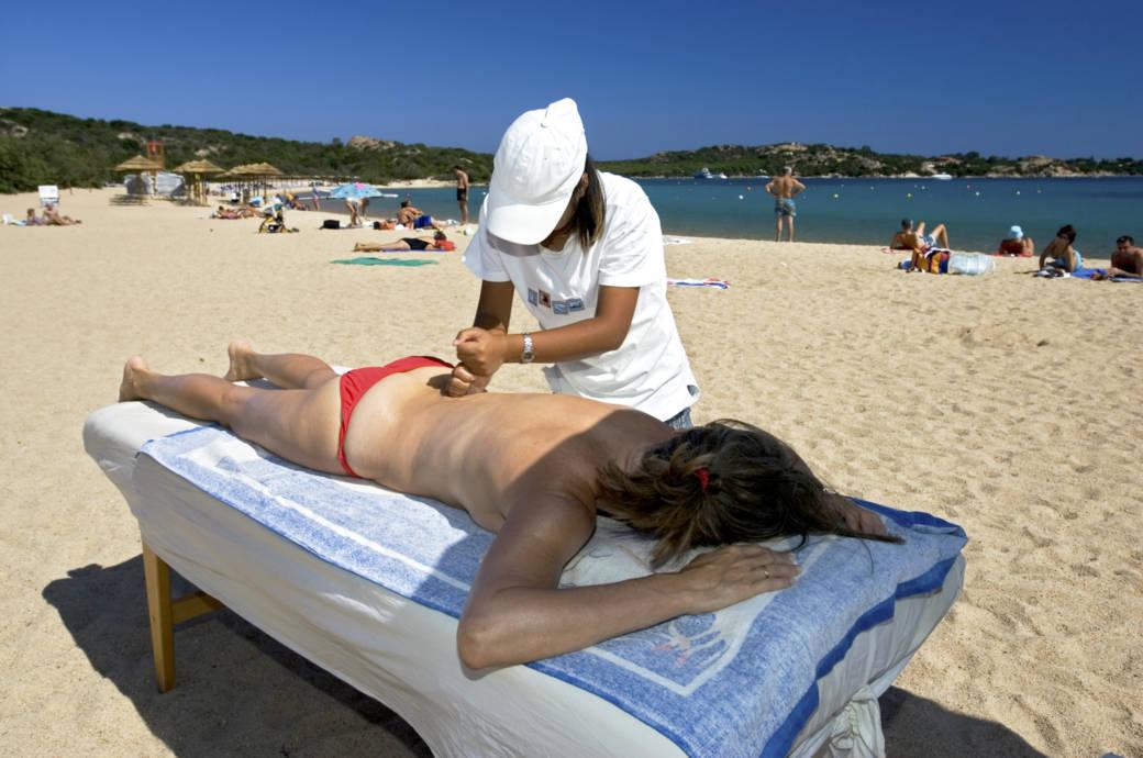 Frau lässt sich am Strand massieren