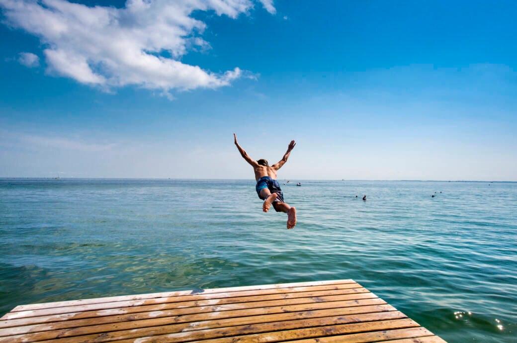 Ein Badeurlauber springt auf der Ostseeinsel Fehmarn ins Meer