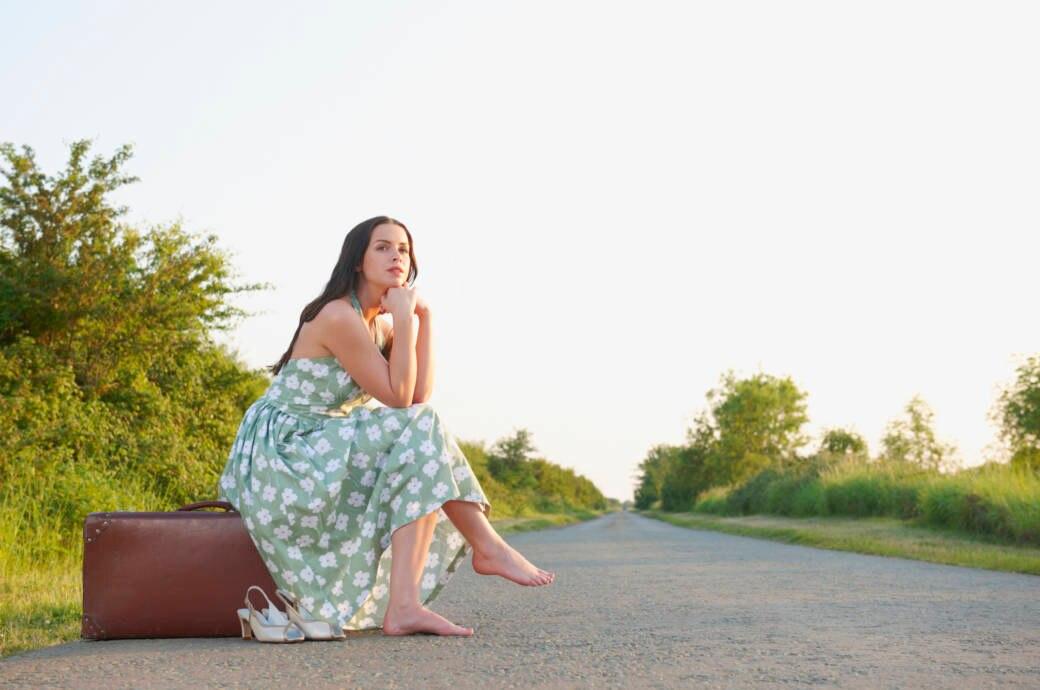 Frau sitzt auf ihrem Koffer