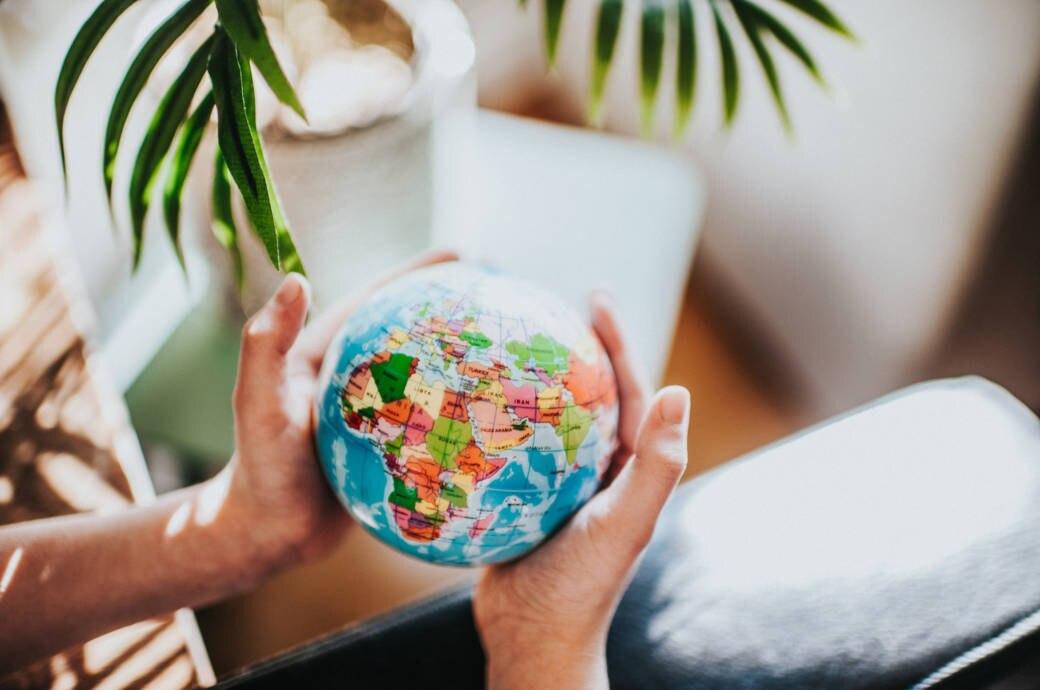 Mann hält Globus mit Länderumrissen