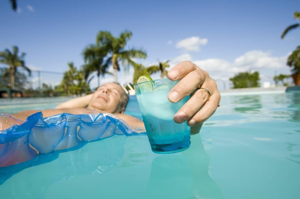 Mann mit Getränk im Pool