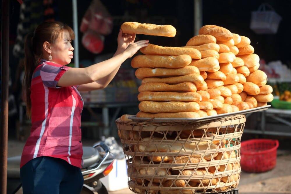 Eine Frau verkauft Binh Mi auf einem Markt in Vietnam