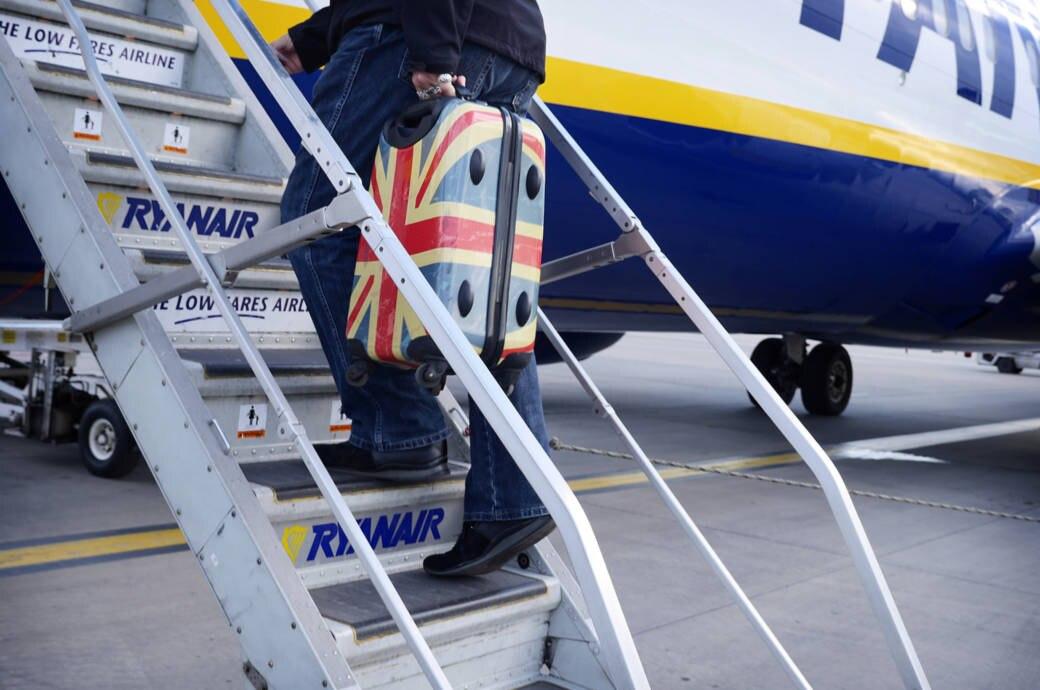 Passagier mit Hanggepäckkoffer steigt in Ryanair-Maschine ein