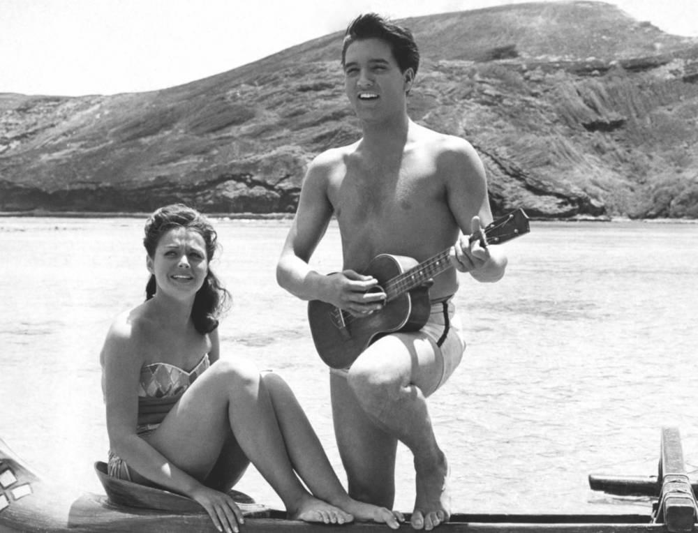 """Elvis Presley in dem Film """"Blue Hawaii"""". Im Hintergrund sind gut erkennbar die Hügel, die die Bucht umgeben"""