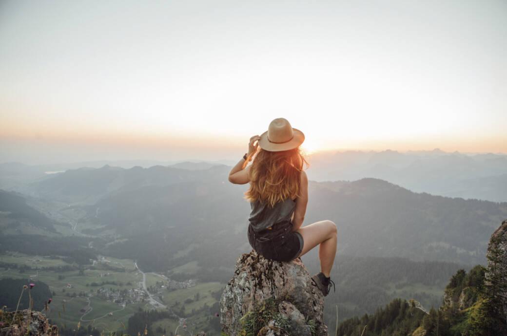 Alleinreisende Frau blickt auf Berge