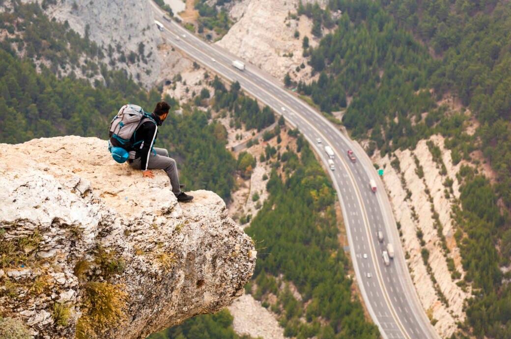 Ein Mann sitzt auf einem Felsen und Blick tief herab