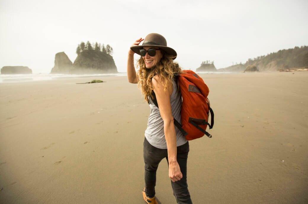 Eine Frau spaziert an einem Strand