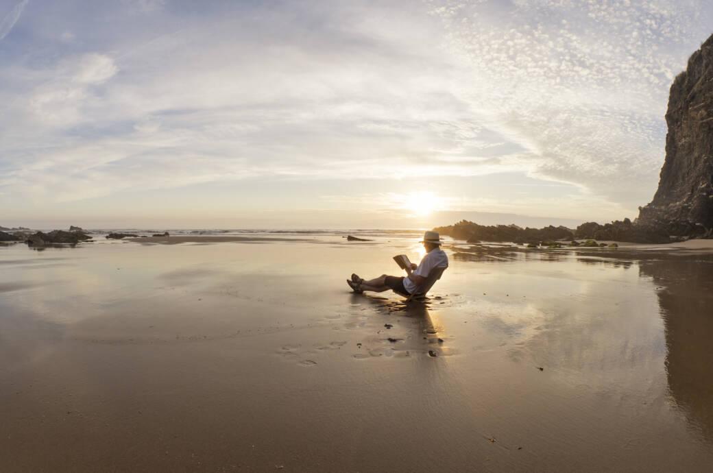 Ein Rentner sitzt am Strand und liest