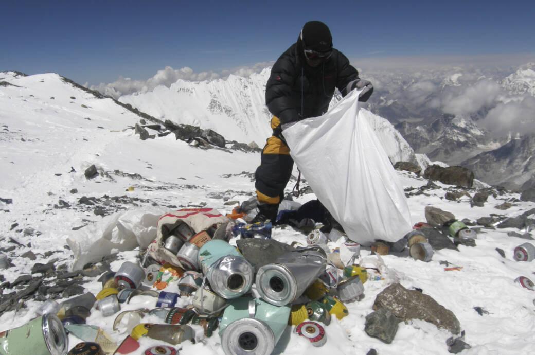 Ein Sherpa sammelt auf dem Mount Everest Müll auf