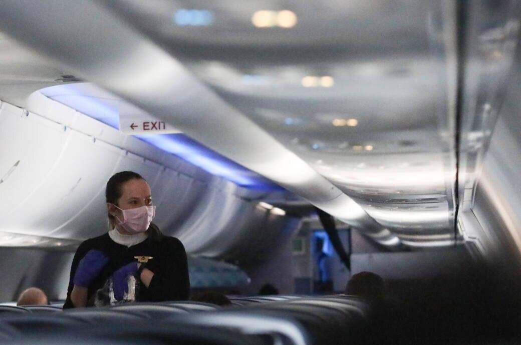 Flugbegleiterin mit Mundschutz im Flugzeug