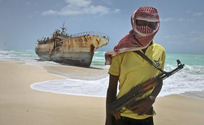 Ein Pirat mit Kalaschnikow am Strand von Hobyo vor einem Schiffswrack