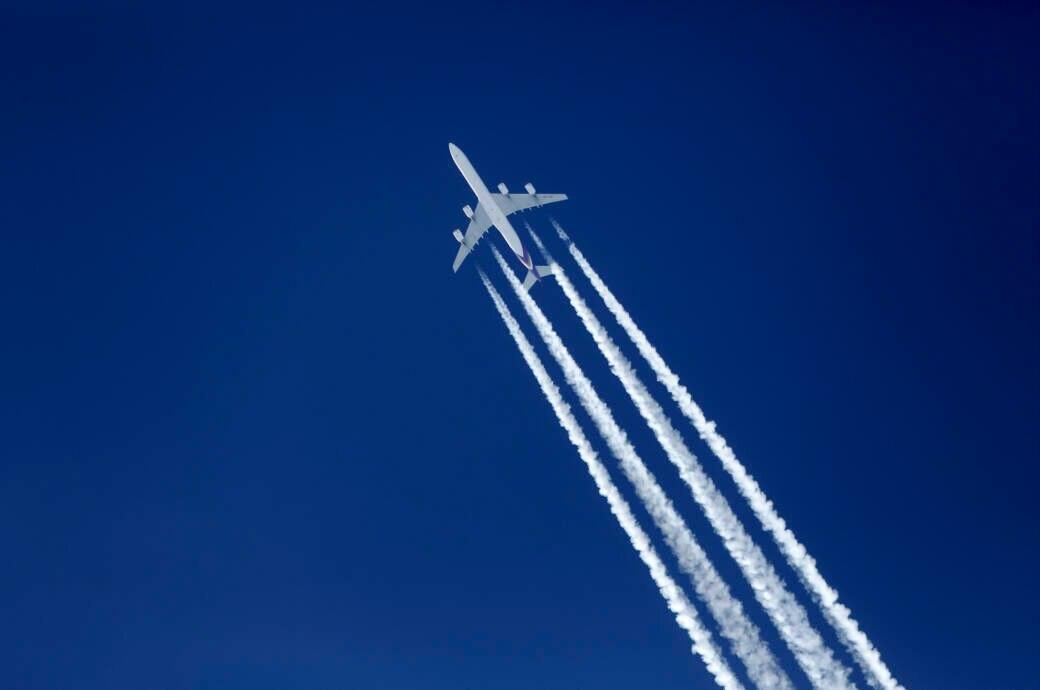 Ein Flugzeug Airbus A340 in der Luft mit Kondenzstreifen