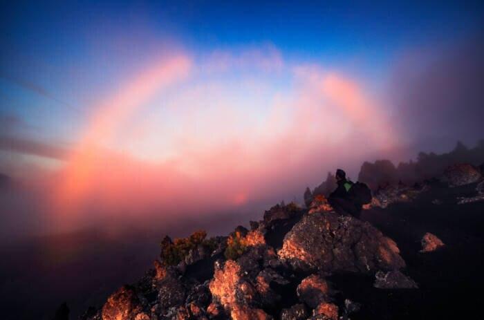 Ein Nebelbogen über der kanarischen Insel La Palma wird von der Abendsonne in rotes Licht getaucht
