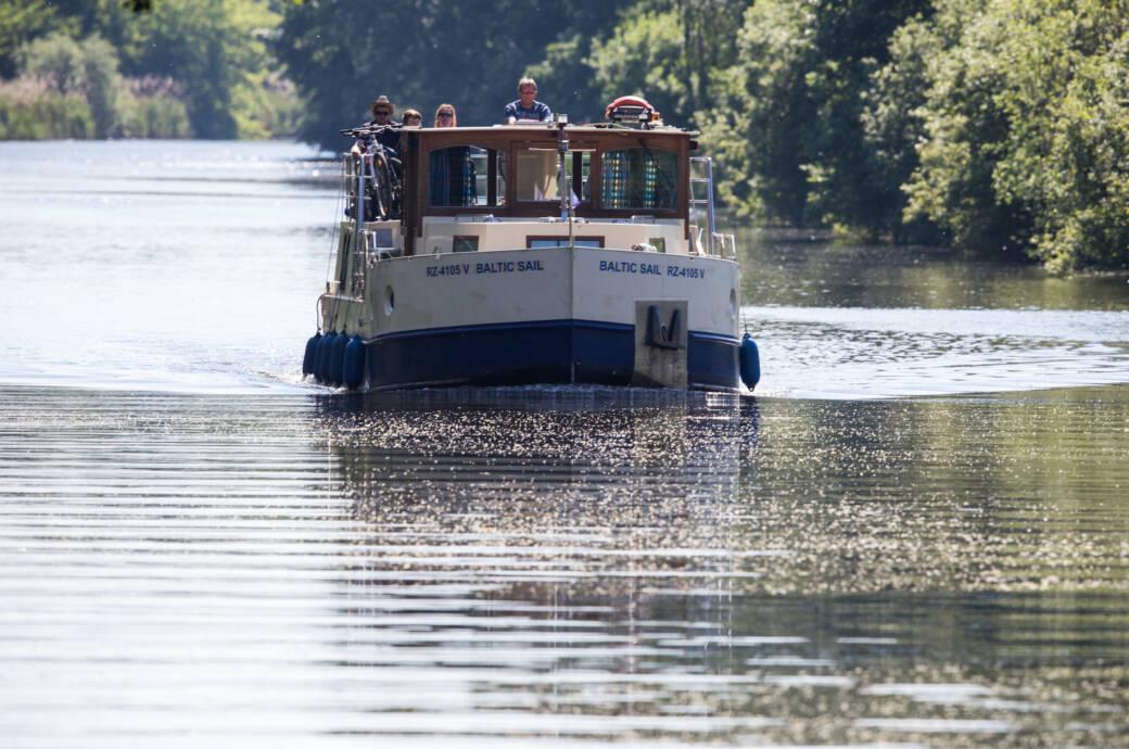 Ein Hausboot auf dem Mirow Kanal in Mecklenburg-Vorpommern unterwegs