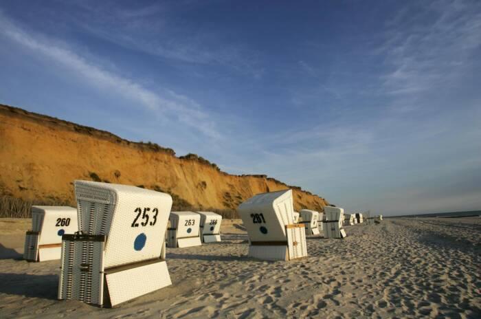 Strandkörbe stehen unter einem Kliff